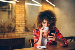 Young woman at cafe drinking coffee and using mobile phone. text marketing concept