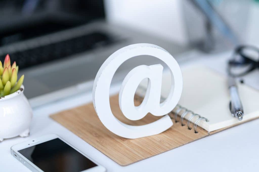 Email comcept. Contact us for feedback. Desktop with notepad, smartphone, glasses and email symbol. Top view