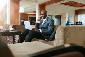 Happy young businessman sitting on sofa working using cell phone and laptop. African male executive waiting in hotel lobby.